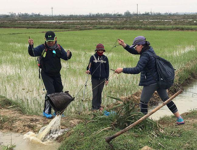 Vợ chồng bà Katherine Nguyễn và ông Dean Nguyễn cùng tát nước. Ảnh: Nhân vật cung cấp.