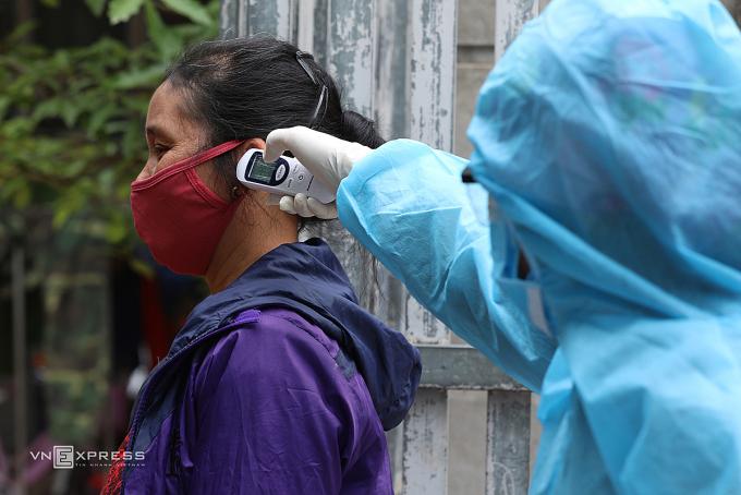 Nhân viên y tế đo thân nhiệt người dân Hà Nội. Ảnh: Ngọc Thành.