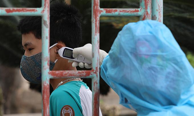 Đo nhiệt độ cho người dân thôn Hạ Lôi, xã Mê Linh, huyện Mê Linh, Hà Nội. Ảnh: Ngọc Thành.