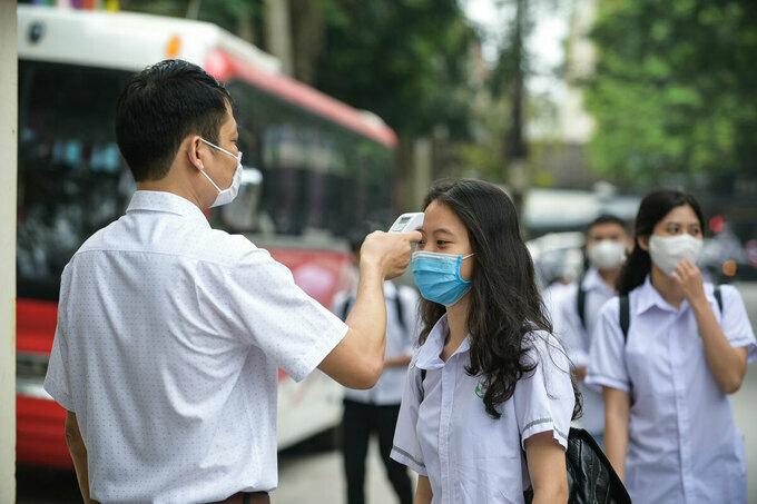Giáo viên đo thân nhiệt tại cổng trường THPT Tô Hiến Thành, Thanh Hoá. Ảnh:Lê Hoàng.