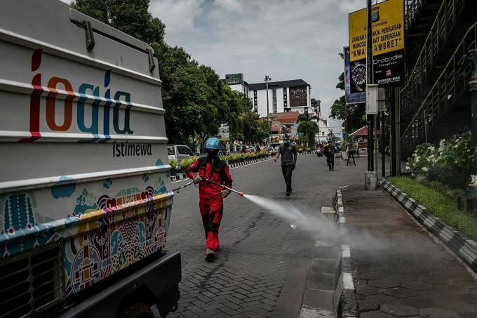 Nhân viên y tế tiêu độc khử trùng trên đường phố Indonesia vào giữa tháng 3. Ảnh: NY Times