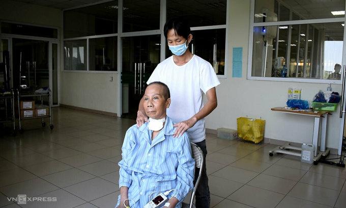 Nữ bệnh nhân ngồi đón nắng cùng con trai chiều 11.5. Ảnh:Chi Lê.