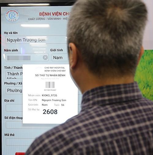 Thứ trưởng Y tế Nguyễn Trường Sơn thử nghiệm hệ thống lấy số thự tự tại Bệnh viện Chợ Rẫy chiều 18/5. Ảnh: N.H