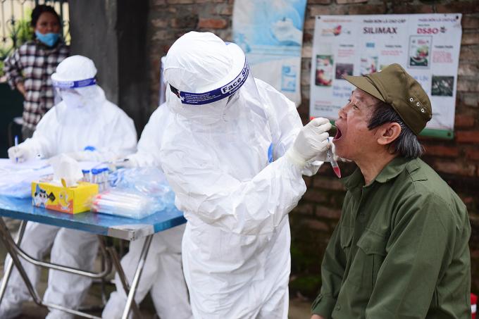 Người dân thôn Hạ Lôi (Mê Linh) đeo khẩu trang, ngồi cách nhau khoảng hơn một mét để chờ đến lượt lấy mẫu bệnh phẩm. Ảnh: Giang Huy