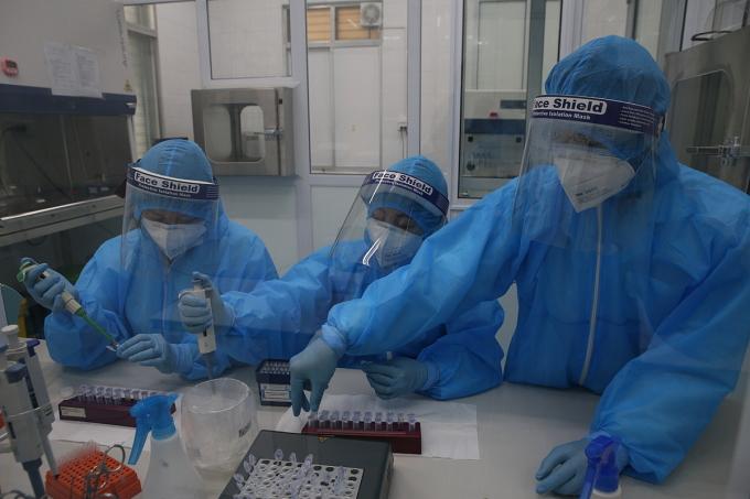 Các kỹ thuật viên làm việc liên tục 5 giờ để sàng lọc một mẻ mẫu phẩm của những trường hợp tiếp xúc gần với với người bệnh hoặc nghi ngờ có liên quan tới Covid-19. Ảnh:Văn Hải