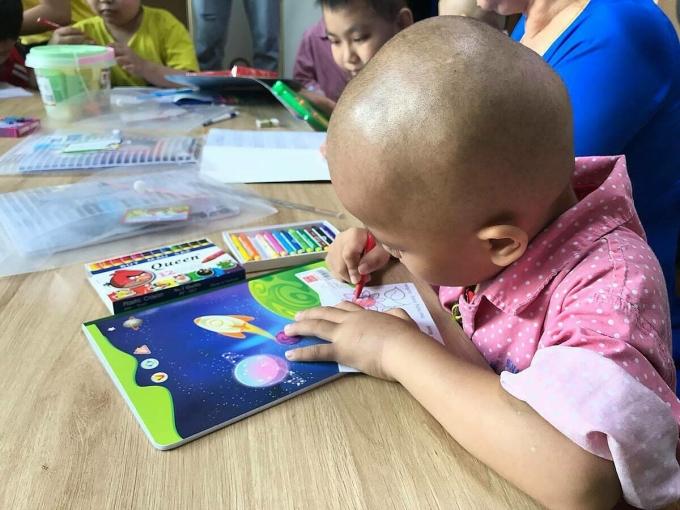 Một bệnh nhi ung thư đang học tô màu tại lớp học Hạnh phúc. Ảnh: Thái Hà.