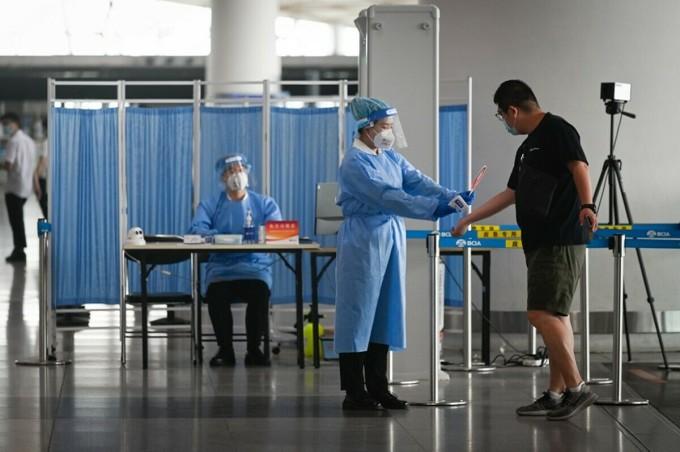 Đo nhiệt độ hành khách tại Sân bay Quốc tế Bắc Kinh, ngày 17/6. Ảnh: AFP