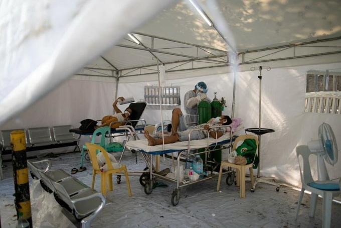 Nhân viên y tế thay bình oxy cho bệnh nhân tại một lều điều trị dã chiến ởManila, tháng 4. Ảnh:Reuters