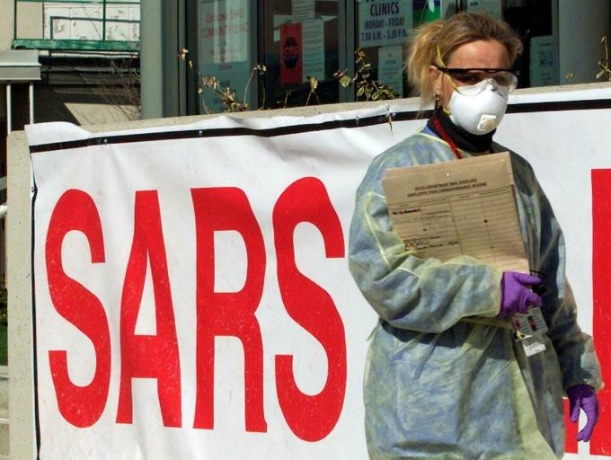 Y tá mặc đồ bảo hộ bên ngoài một phòng khám tại Toronto, Mỹ, trong dịch Sars năm 2003. Ảnh: Reuters