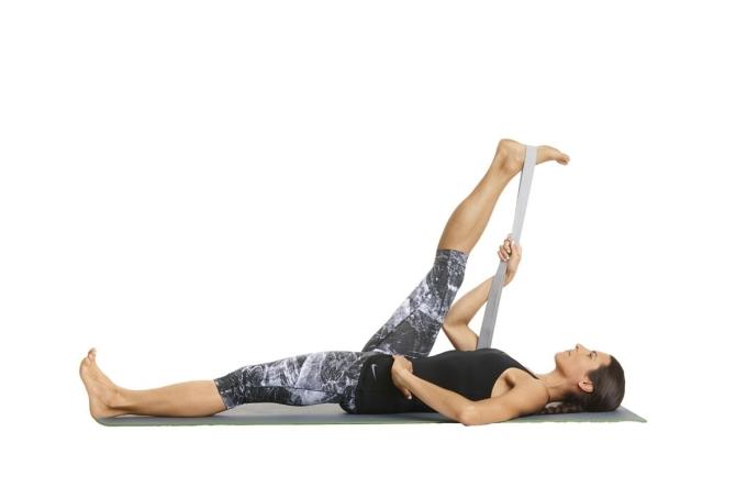 Đầu tiên, runner nằm ngửa trên thảm, gập chân lại, hai lòng bàn chân áp xuống sàn. Tiếp đó quàng dây đeo yoga (có thể thay bằng thắt lưng hoặc dây xích chó) qua lòng bàn chân phải, đưa lên cao, còn chân trái duỗi thẳng lên sàn. Kéo dây sao cho chân phải đưa gần về phía mặt, rôi nghiêng chân sang phải, về giữa và sang trái, thân người vẫn giữ nguyên. Tập trong 10 nhịp thở, lặp lại trên chân kia. Tư thế này giúp kéo dài nhóm cơ đùi sau.