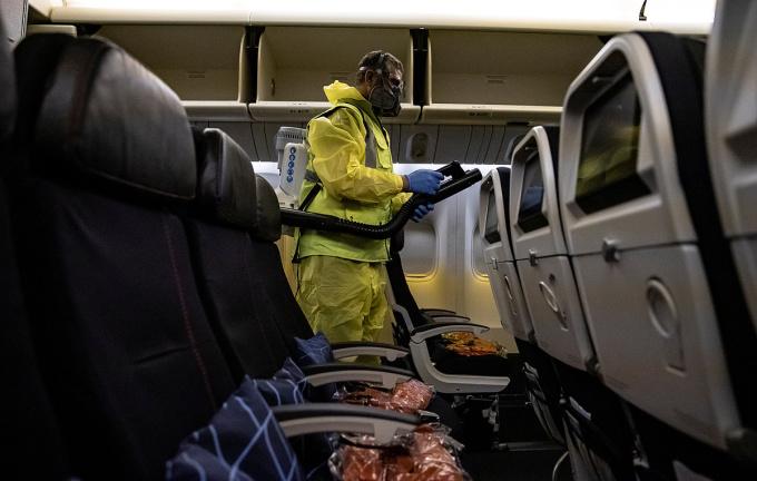 Nhân viên tại Sân bay Charles de Gaulle khử khuẩn khoang hành khách, ngày 14/5. Ảnh: Reuters