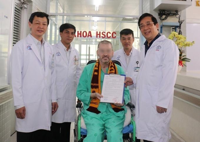 Bệnh nhân phi công nhận giấy ra viện và chứng nhận 9 lần âm tính nCoV, cùng Cục trưởng Khám chữa bệnh Lương Ngọc Khuê (bìa phải) và các bác sĩ Bệnh viện Chợ Rẫy, sáng 11/7. Ảnh do bệnh viện cung cấp.