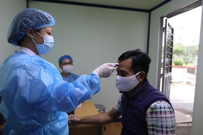 Bác sĩ đo thân nhiệt cho bệnh nhân tại Hà Nội tháng 3/2020. Ảnh: Ngọc Thành