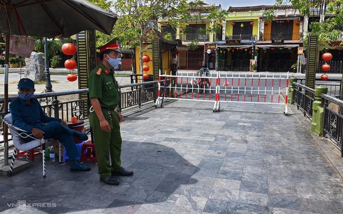 Lực lượng chức năng Hội An dựng hàng rào phong tỏa trên cầu An Hội, đường ra vào khu phố nơi cư trú của bệnh nhân 428, sáng 30/7. Ảnh: Đắc Thành.