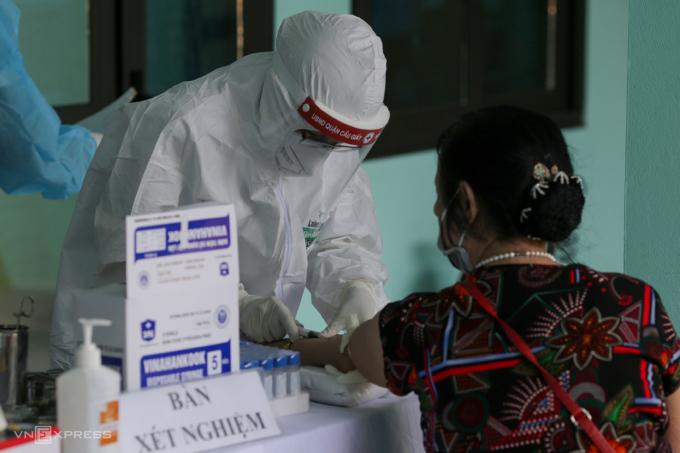 Nhân viên y tế phường Yên Hòa, quận Cầu Giấy, Hà Nội, lấy mẫu máu xét nghiệm người về từ Đà Nẵng, ngày 30/7. Ảnh: Tất Định.