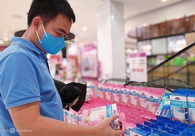 Một hành khách tìm mua khẩu trang ở siêu thị. Ảnh: Minh Anh