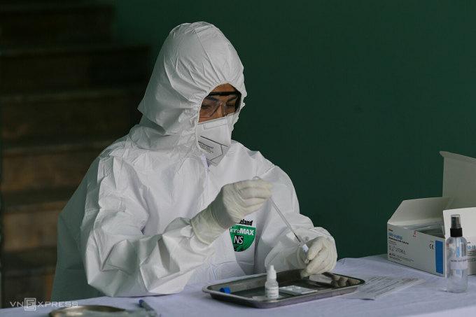 Nhân viên y tế phường Yên Hòa, quận Cầu Giấy, Hà Nội lấy mẫu máu xét nghiệm cho người về từ Đà Nẵng. Ảnh: Tất Định.