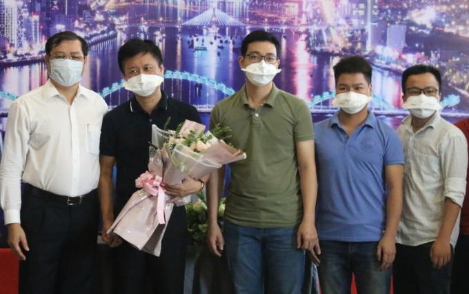 Ông Huỳnh Đức Thơ (áo trắng) tặng hoa cảm ơn các bác sĩ, điều dưỡng cuối cùng rời khỏi Đà Nẵng. Ảnh: Diệu Bình.