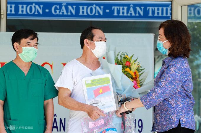 Bệnh nhân 936 (áo trắng) nhận hoa chúc mừng từ Giám đốc Sở Y tế Ngô Thị Kim Yến. Ảnh: Nguyễn Đông.