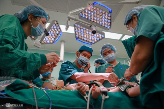 Bác sĩ Định (đeo tai nghe) trực tiếp khám cho hai bé trước cuộc mổ ngày 15/7. Ảnh: Hữu Khoa.