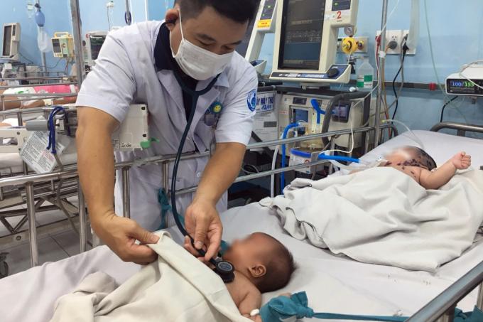 Bác sĩ Quy khám cho hai bệnh nhi nặng nằm ở phòng cấp cứu. Ảnh: Thư Anh.