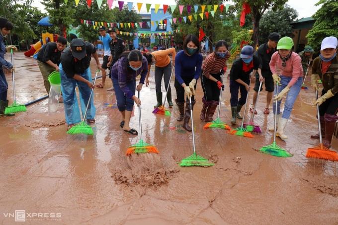 Các cô giáo tại Cẩm Xuyên, Hà Tĩnh đang dùng chổi đẩy bùn đất từ trong sân ra ngoài đường, sau đó dội nước để bùn trôi xuống ruộng. sau khi bão đi qua. Ảnh: Đức Hùng