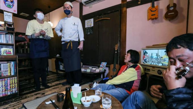 Hiroaki Murata (thứ hai từ trái sang) và vợ nói chuyện với khách hàng và nhạc công trong quán rượu nhỏ ở Tokyo, ngày 13/11. Ảnh: Nikkei