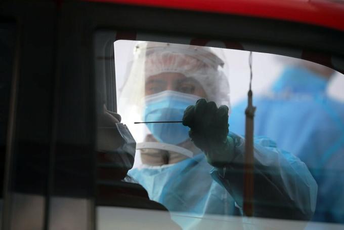 Nhân viên y tế lấy mẫu dịch mũi của một tài xế tại trạm xét nghiệm lưu động ở thành phố Oakland, California. Ảnh: NY Times
