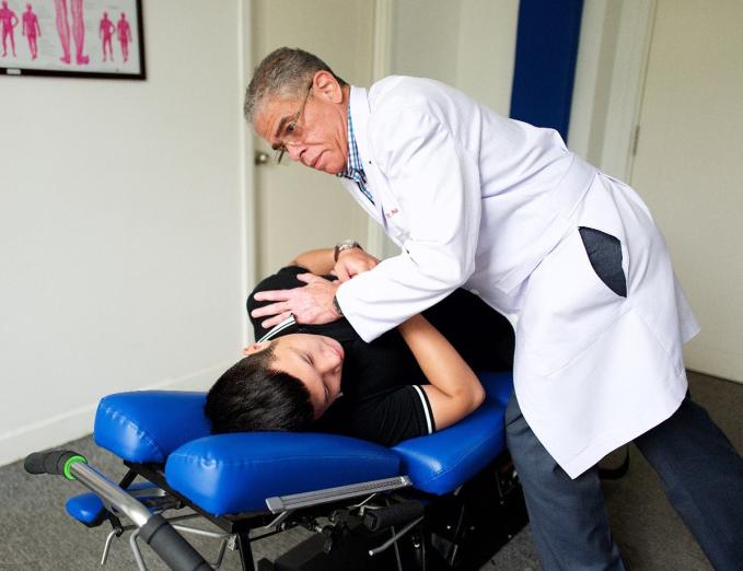Bác sĩ Aubrey Gail thực hiện thủ thuật nắn chỉnh cột sống lưng cho bệnh nhân. Ảnh: Trà Mi.