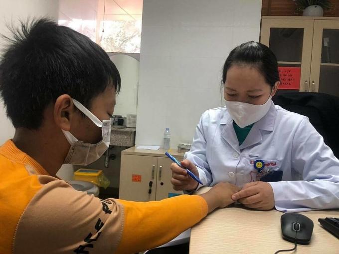 Bác sĩ khám cho bệnh nhi bị mày đay vẽ nổi. Ảnh: Nguyễn Hương.