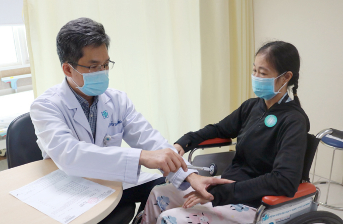 Bác sĩ Thắng thăm khám cho người bệnh sau tái thông mạch máu và điều chỉnh liều kháng đông cho phù hợp để bệnh tiếp tục dùng thuốc lâu dài, dự phòng tái đột quỵ. Ảnh: Minh Trí.