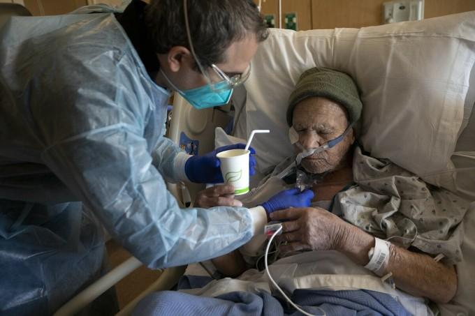 Y tá Kevin Deegan, bên trái, cho Juan Legaspi-Lozano, 90 tuổi, một ngụm nước nhỏ tại Trung tâm Y tế Providence Holy Cross ở Mission Hills, California. Ảnh: LA