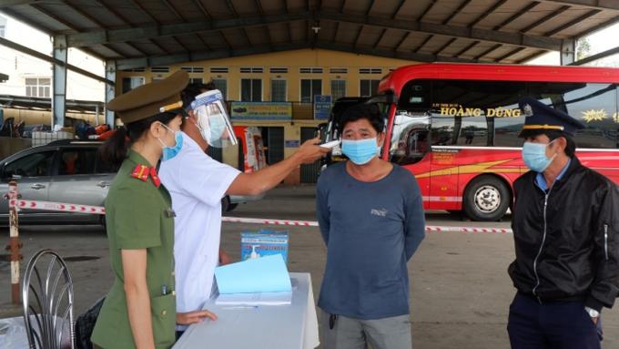 Đo thân nhiệt cho hành khách tại Bến xe Trung tâm Quy Nhơn. Ảnh: Thu Phương.