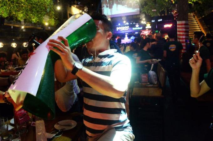 Người đàn ông uống bia bằng tháp tại TP HCM. Ảnh: Hoang Dinh Nam/AFP.