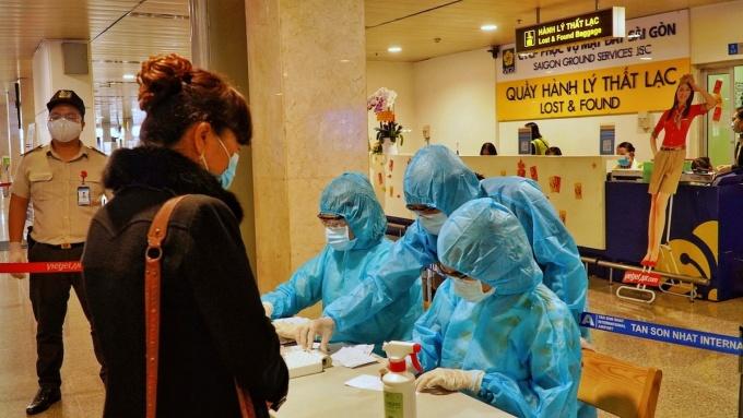 Hành khách thực hiện khai báo y tế khi đến sân bay Tân Sơn Nhất, TP HCM. Ảnh: HCDC