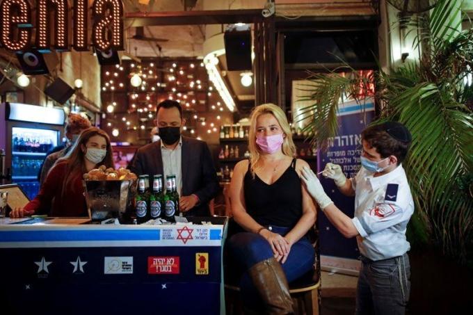 Một phụ nữ được tiêm vaccine tại quán bar ở thành phố Tel Aviv, ngày 18/2. Ảnh: Reuters