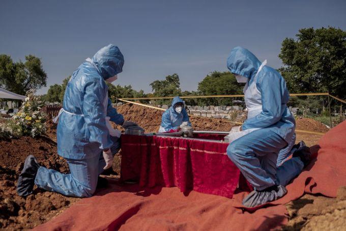 Nhân viên nhà tang lễ chôn cất một bệnh nhân tử vong do mắc Covid-19 tại  Pretoria, Nam Phi. Ảnh: WSJ