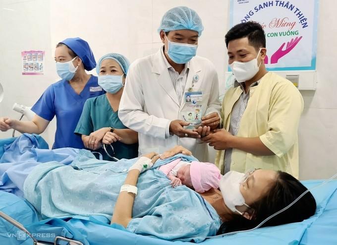 Bác sĩ Hồng Công Danh, Phó giám đốc Bệnh viện Từ Dũ tặng chiếc khánh lưu niệm cho những em bé chào đời ngày 27/2 tại bệnh viện. Ảnh: Lê Phương.