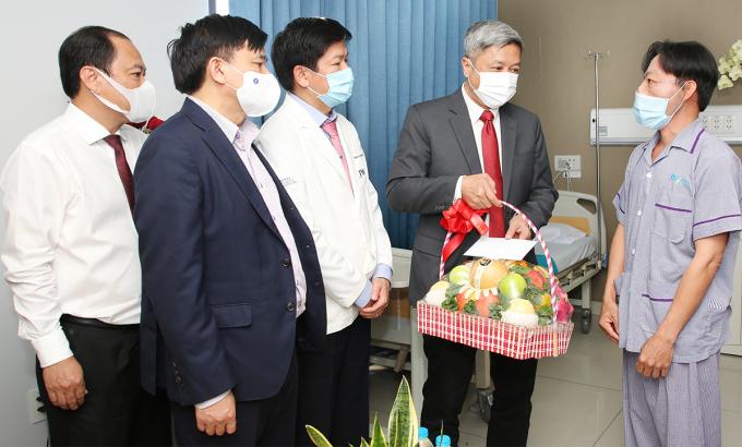 Thứ trưởng Y tế Nguyễn Trường Sơn (thứ hai từ phải sang) tặng quà, chúc mừng bệnh nhân Lê Văn Mến chiều 5/3. Ảnh: Lê Phương.