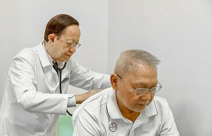 Phó giáo sư Phạm Nguyễn Vinh thăm khám cho bệnh nhân bị bệnh tim mạch. Ảnh: Phong Lan.
