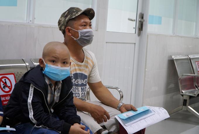 Long và bố hồi hộp ngồi chờ tái khám trước khi làm thủ tục nhập viện, chuẩn bị cho ca ghép tế bào gốc vào tháng 4. Ảnh: Thư Anh.