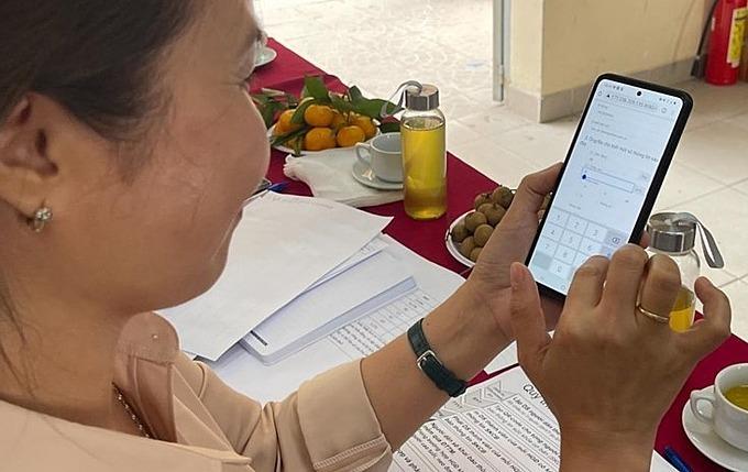 Trưởng trạm Y tế phường 27 dùng mã QR code để tự khai báo thông tin y tế cơ bản vào hồ sơ sức khoẻ điện tử của riêng mình trên điện thoại di động ngày 2/4. Ảnh do Sở Y tế TP HCM cung cấp.