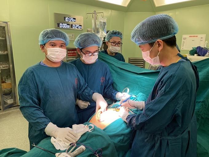 Các bác sĩ thực hiện cắt khối u lớn trong ổ bụng bệnh nhân. Ảnh: Mai Thanh.