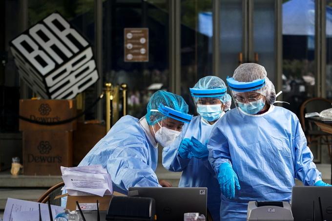 Nhân viên y tế lấy mẫu xét nghiệm nCoV của người dân trước một quán bar ở Bangkok. Ảnh: Reuters