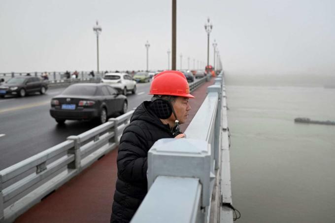 Tình nguyện viên Chen Si trên cầu Nam Kinh. Ảnh: AFP