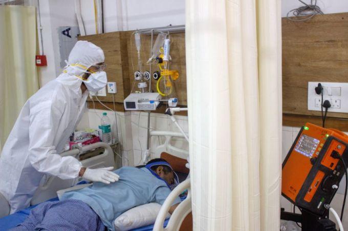 Bác sĩ Murtuza Ghiya giúp một bệnh nhân Covid-19 nằm sấp để phổi nhận được nhiefu oxy hơn. Ảnh: Straits Times.