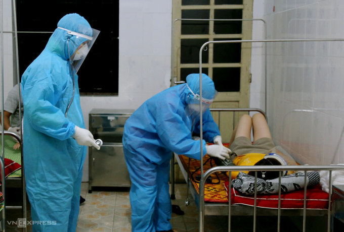 Bác sĩ lấy mẫu xét nghiệm nCoV đối với nữ bệnh nhân khi đang điều trị tại Bệnh viện Đa khoa khu vực cửa khẩu quốc tế Cầu Treo, tối 30/4. Ảnh: Đức Hùng