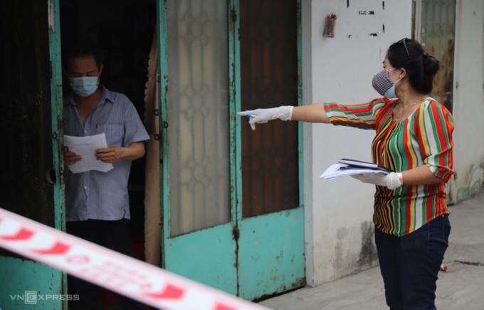 Nhân viên trung tâm y tế quận 12 (bìa phải) đến đưa giấy khai báo y tế cho người dân trong khu phong tỏa, cách ly tại nhà hồi tháng 2/2021. Ảnh: Đình Văn.