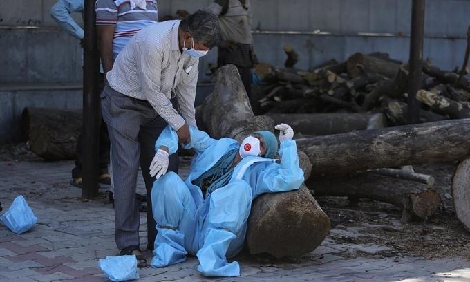 Người thân một bệnh nhân nhiễm nCoV gục ngã tại lễ hỏa táng ở Jammu, Ấn Độ, ngày 25/4. Ảnh: AP.