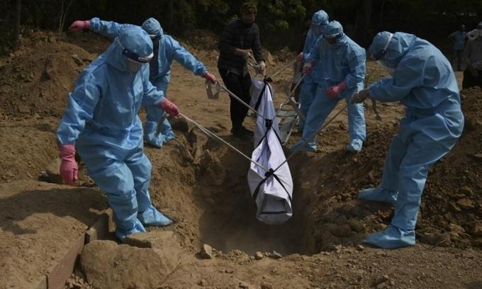 Thân nhân mặc đồ bảo hộ chôn cất bệnh nhân Covid-19 tại một nghĩa trang ở New Delhi, Ấn Độ, hôm 30/4. Ảnh:Reuters.